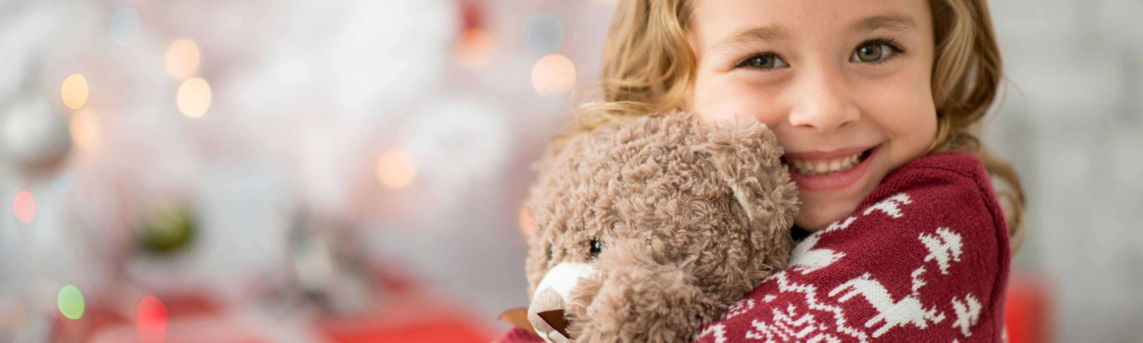 Small child holding a stuffed bear.